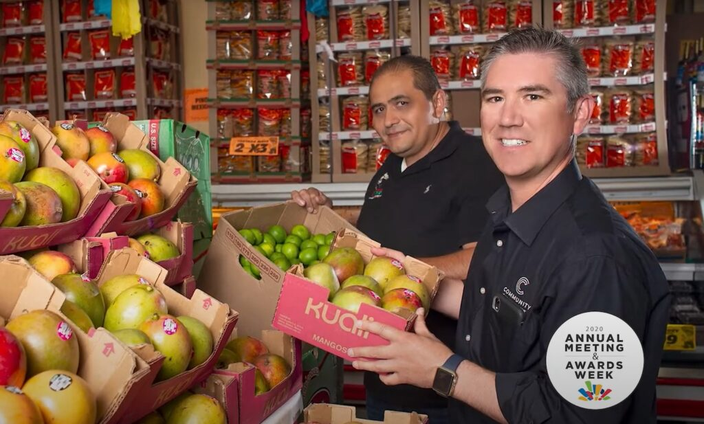 A picture of Jesus Higareda, owner of Supermex El Pueblo grocery market, stands in front of a fruit stand beside his commercial banker Jesus Melendez.