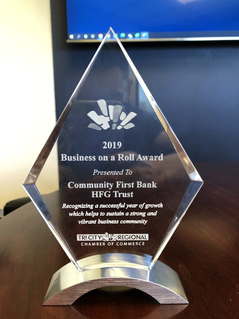 A triangular, glass award trophy, naming Community First Bank & HFG Trust as the Tri-Cities Regional Chamber of Commerce's 2019 Business on a Roll recipient.